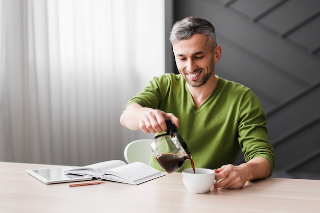 Uomo in camicia verde versando caffè e sorrisi