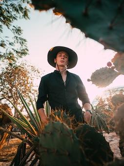Uomo in cappello nero vicino al cactus