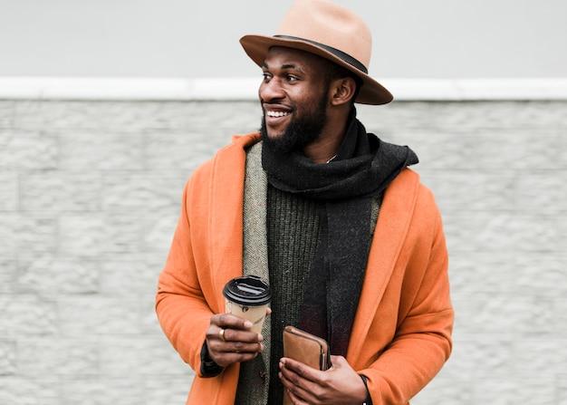 Uomo in cappotto arancio che tiene una tazza di caffè all'aperto