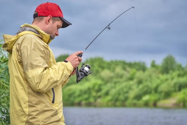 Uomo in cappotto che pesca in un lago