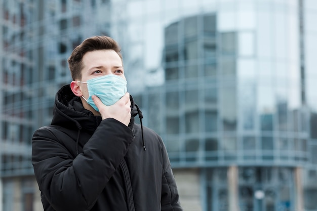 Uomo in città che indossa giacca e maschera medica