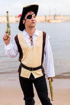Uomo in costume da pirata sollevato fino alla cima della pistola giocattolo.