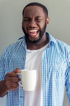 Uomo in eleganti abiti casual è in possesso di tazza e urlando