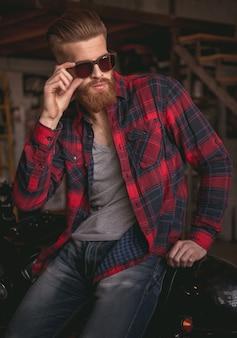 Uomo in eleganti abiti casual e occhiali da sole.