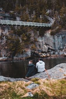 Uomo in felpa con cappuccio grigia che si siede sulla roccia vicino al corpo idrico durante il giorno
