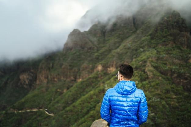 Uomo in giacca blu rilassante in montagna con il cielo nuvoloso