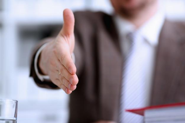 Uomo in giacca e cravatta che offre handshake