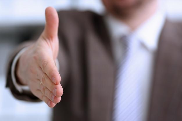 Uomo in giacca e cravatta che offre la mano come ciao