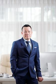 Uomo in giacca e cravatta in piedi al suo tavolo ufficio mostrando il suo successo