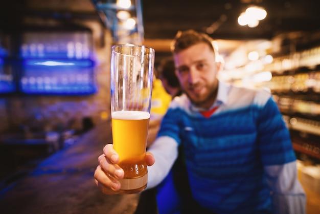 Uomo in maglia che tiene la pinta di birra in su in celebrazione della vittoria delle sue squadre.