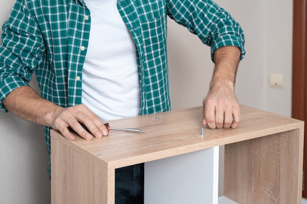 Uomo in maglietta bianca e camicia a quadri torce il catenaccio con la chiave a forma di z.