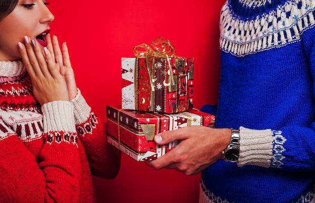 Uomo in maglione islandese dando la sua ragazza confezioni regalo. concetto di celebrazione di natale.