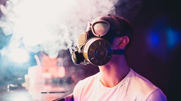 Uomo in maschera antigas fumare un narghilè e soffiare il fumo