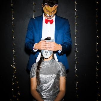 Uomo in maschera di volpe che chiude gli occhi alla donna nella maschera di gatto