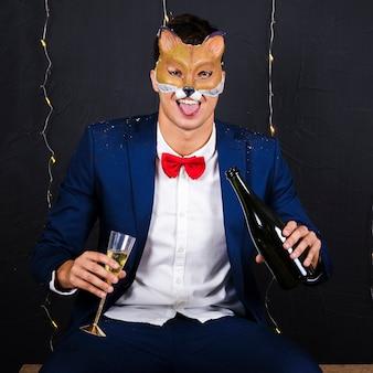 Uomo in maschera di volpe che tiene in mano un bicchiere e una bottiglia di champagne