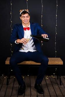 Uomo in maschera di volpe sulla testa con vetro e bottiglia di champagne