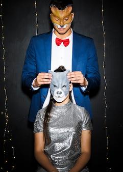 Uomo in maschera di volpe vicino donna nella maschera di gatto