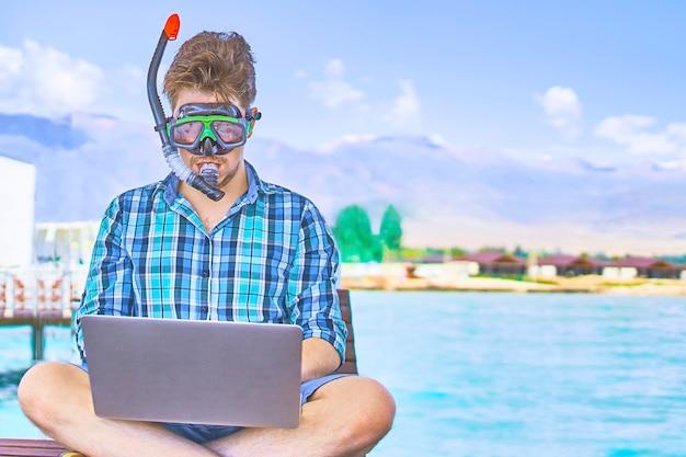 Uomo in maschera subacquea durante il fine settimana, in mare, lavorando su un computer portatile