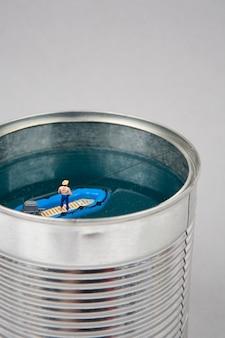 Uomo in miniatura che pesca in una lattina