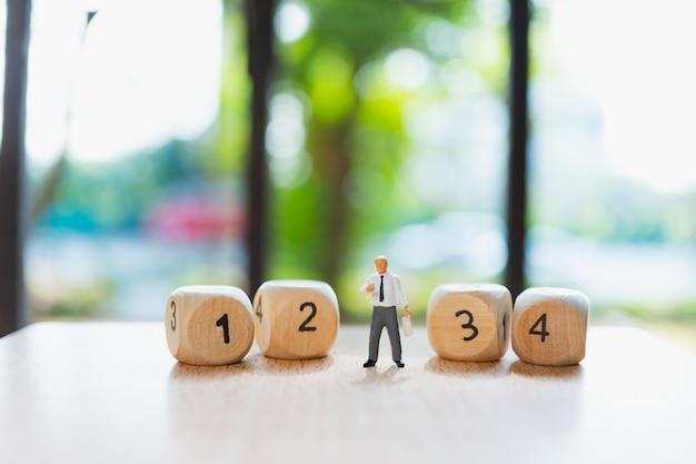 Uomo in miniatura che sta con i numeri di legno