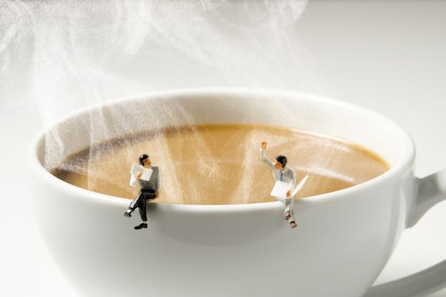 Uomo in miniatura di affari che si siede sul bordo bianco caldo della tazza di caffè del vapore