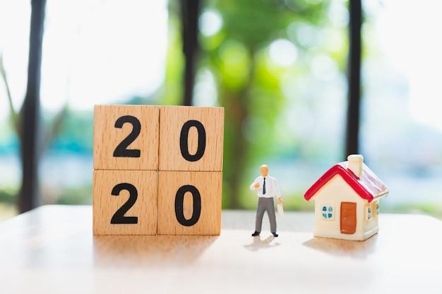 Uomo in miniatura in piedi con mini casa e l'anno 2020 in blocchi di legno
