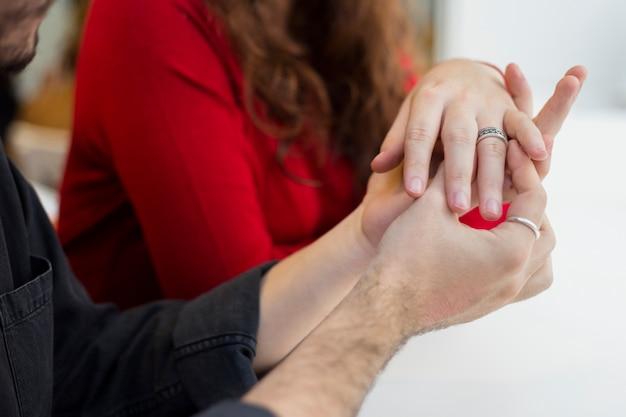 Uomo in nero che mette fede nuziale sul dito della donna