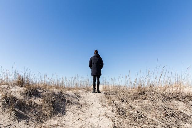 Uomo in nero che resta sulla collina su sfondo blu cielo