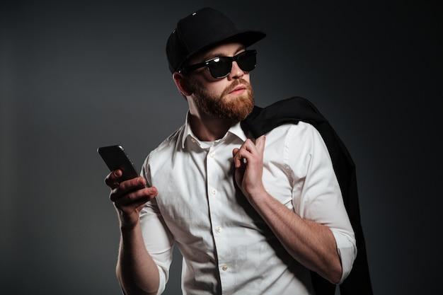 Uomo in occhiali da sole e camicia che tiene telefono e distogliere lo sguardo