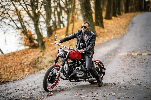 Uomo in occhiali da sole e giacca di pelle che si siede su una moto sulla strada