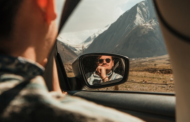 Uomo in occhiali da sole guardando le montagne con finestrino dell'auto riflessa nello specchio
