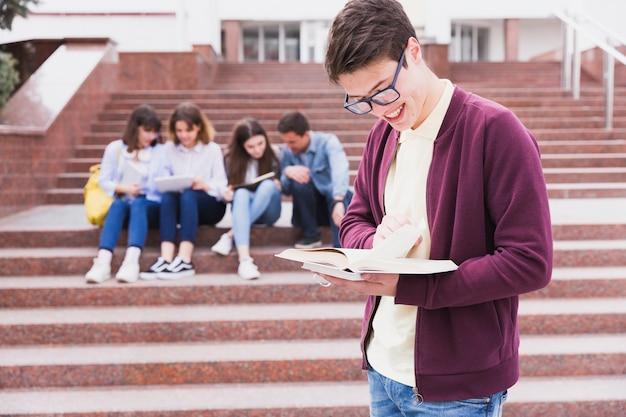 Uomo in occhiali in piedi e leggendo il libro nelle mani