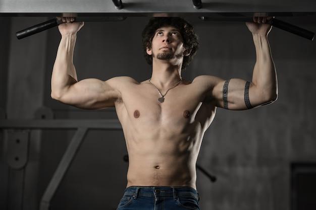 Uomo in palestra che fa allenamento pull-up bodybuilder in palestra