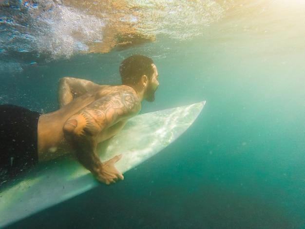 Uomo in pantaloncini immersioni con tavola da surf sott'acqua