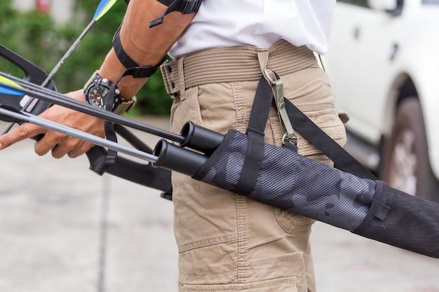Uomo in pantaloni cargo con arco e frecce