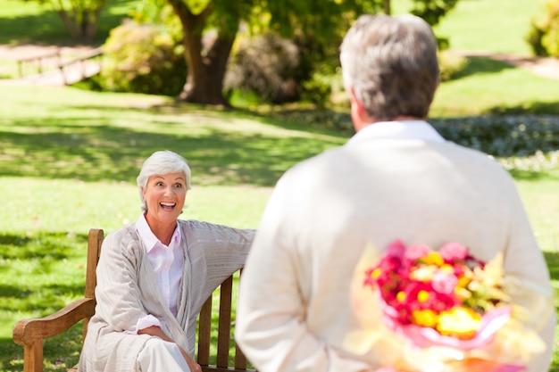 Uomo in pensione che offre fiori a sua moglie