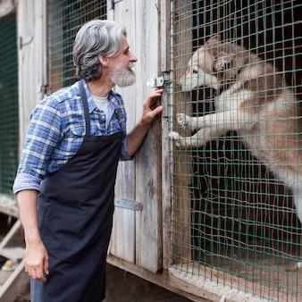 Uomo in piedi accanto alla gabbia del cane