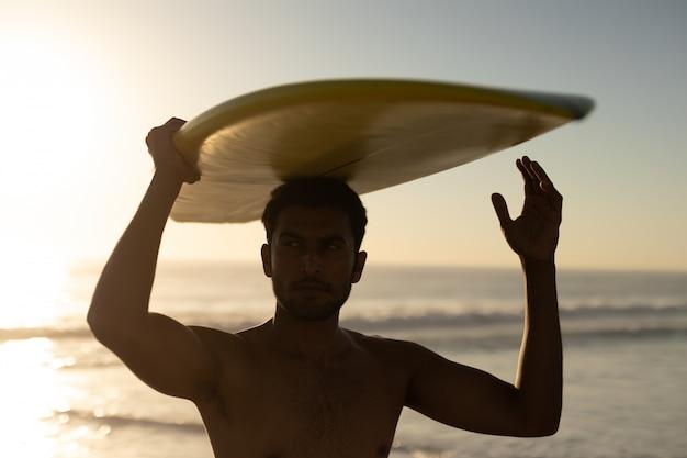 Uomo in piedi con la tavola da surf sulla spiaggia