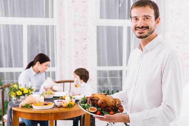 Uomo in piedi con pollo al forno