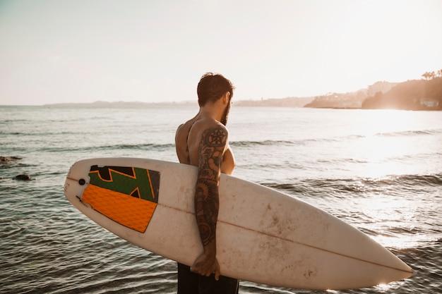 Uomo in piedi con tavola da surf sulla spiaggia