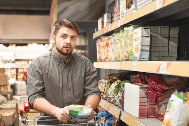 Uomo in piedi con un carrello sul corridoio in un supermercato