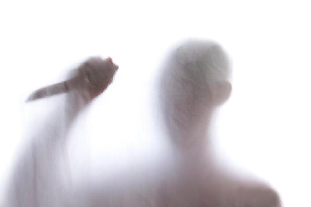 Uomo in piedi dietro un vetro smerigliato e in possesso di un coltello