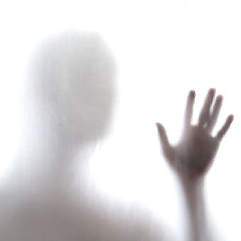 Uomo in piedi dietro un vetro smerigliato