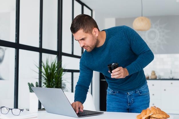 Uomo in piedi guardando portatile