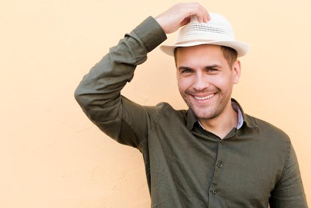 Uomo in piedi su sfondo beige azienda cappello e sorridente