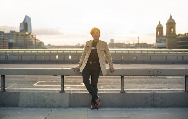 Uomo in piedi su un ponte in una grande città