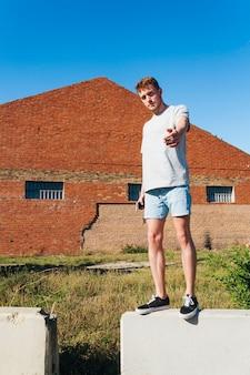 Uomo in piedi sul muro di contenimento e chiamare qualcuno