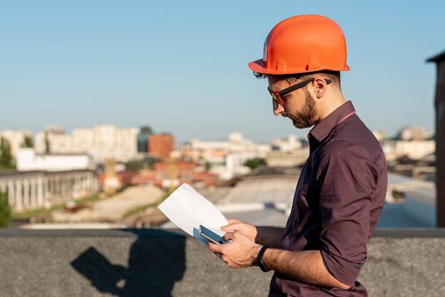 Uomo in piedi sul tetto con il telefono in mano