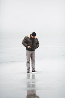 Uomo in piedi sulla pesca del lago ghiacciato