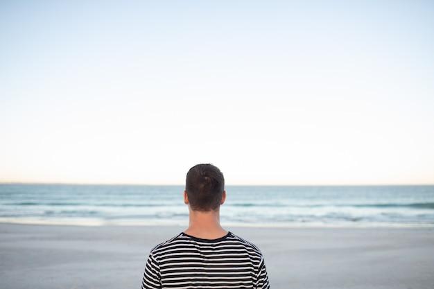 Uomo in piedi sulla spiaggia
